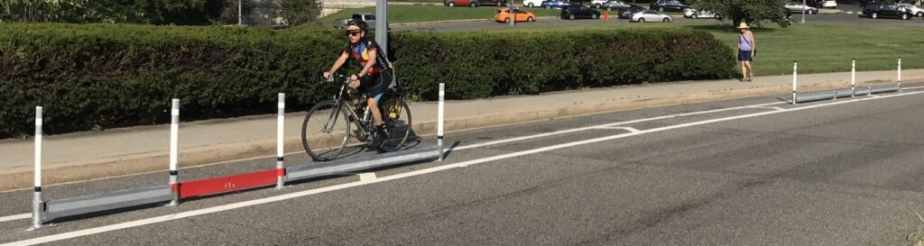 Bicyclist riding behind safety delineator